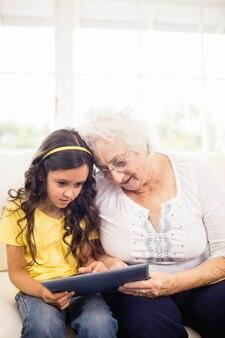 Starke enkelin, die zu hause tablette mit großmutter verwendet