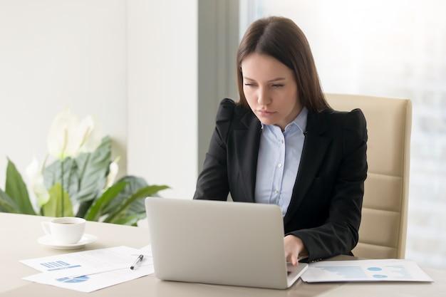 Starke ernste geschäftsfrau, die den bericht, arbeitend mit laptop im büro macht