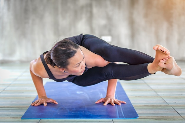 Starke frau des asiatischen auszubildenden, die schwierige yogahaltung in einem konkreten hintergrund übt