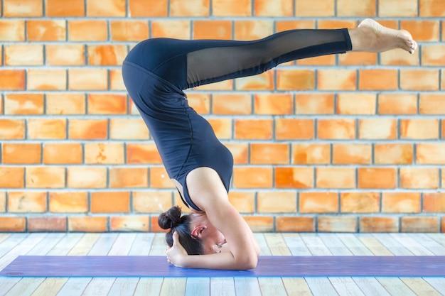 Starke frau des asiatischen auszubildenden, die schwierige yogahaltung übt