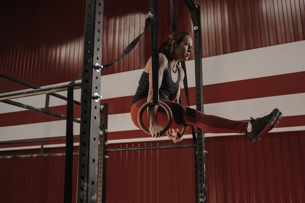 Starke frau, die bauchmuskelübungen auf turnringen im fitnessstudio macht