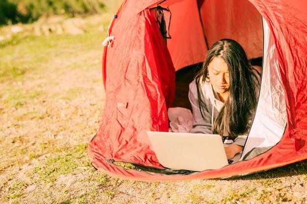 Starke frau, die den laptop liegt im zelt verwendet