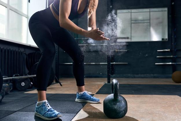 Starke frau, die kettlebells im fitnessstudio hebt