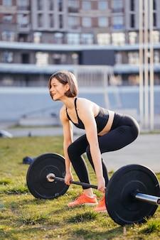Starke frau, die mit langhantel trainiert. nettes mädchen, das für gewichtheben-training vorbereitet. sport, fitnesskonzept.