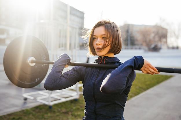 Starke frau, die mit langhantel trainiert. nettes mädchen, das sich auf das gewichthebentraining vorbereitet. sport, fitnesskonzept.