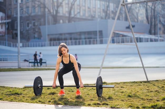 Starke frau, die mit langhantelsport-fitnesskonzept ausübt