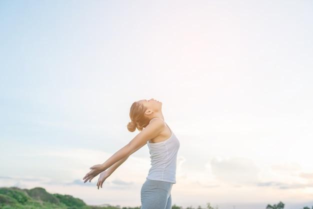 Starke frau ihre arme mit himmel im hintergrund stretching