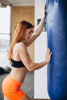 Starke frau in sportkleidung, trainiert mit einer boxbirne in einem fitnessstudio