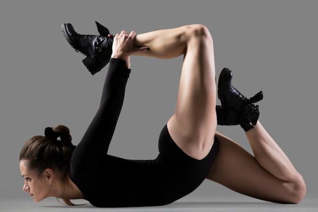 Starke frau mit stiefeln zeigt, die eine yoga-pose
