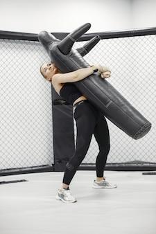 Starke frau trainiert mit mann auf dem selbstverteidigungskurs im fitnessstudio.