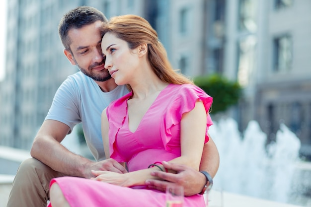 Starke gefühle. angenehmes ehepaar, das in der nähe des brunnens sitzt und sich umarmt