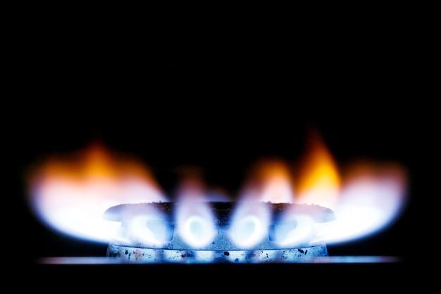Starke gelb-blaue flamme des gasbrenners des küchenherds im dunkeln. unter den text platzieren.