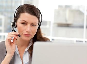 Starke geschäftsfrau, die an ihrem laptop beim nennen arbeitet