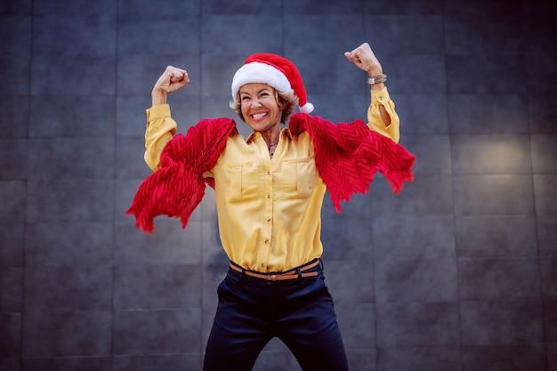Starke gesunde lächelnde kaukasische blonde ältere frau mit kurzen haaren und weihnachtsmütze auf kopf, der vor wand im freien springt.