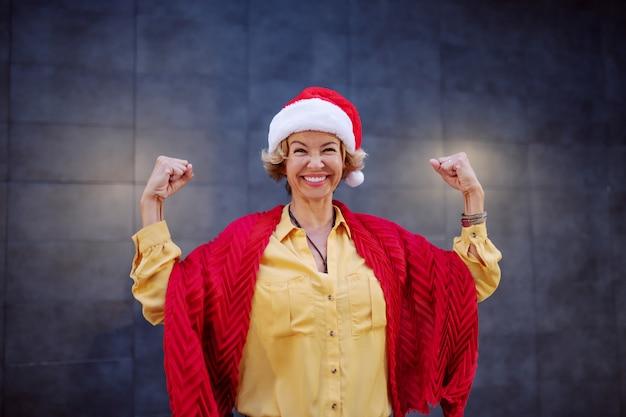 Starke gesunde lächelnde kaukasische blonde ältere frau mit kurzen haaren und weihnachtsmütze auf kopf, die vor wand im freien aufwirft.