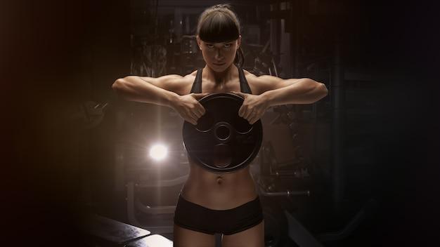 Starke hand der muskulösen frau der eignung, die oben muskeln mit platte pumpt