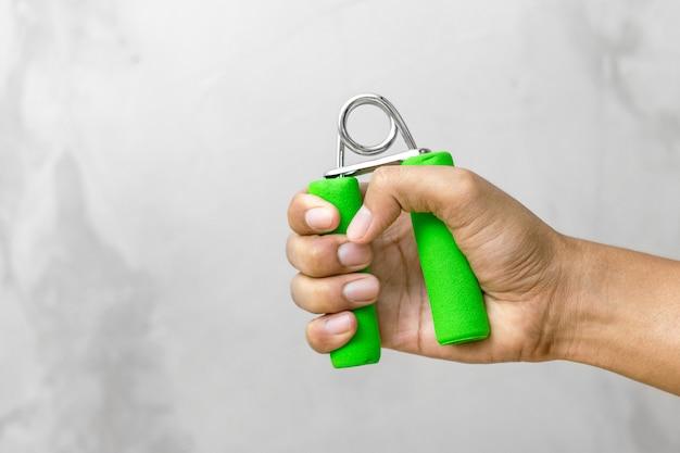 Starke hand, die griff im turnhallenhintergrund hält. griffstärke für übung.