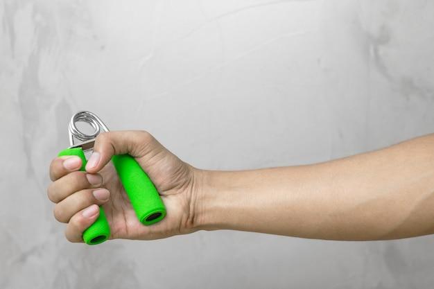 Starke hand, die griff im turnhallenhintergrund hält. halte die kraft für die übung.
