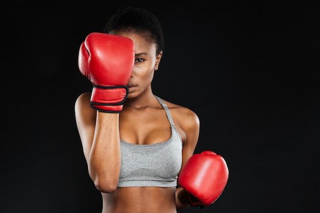 Starke, intensive junge fitnessfrau bedeckte ihr gesicht mit boxhandschuhen über schwarzer wand