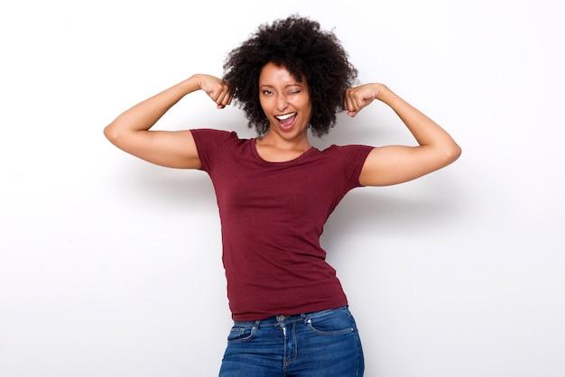 Starke junge afrikanische frau, die beide armmuskeln biegt und auf weißem hintergrund blinzelt