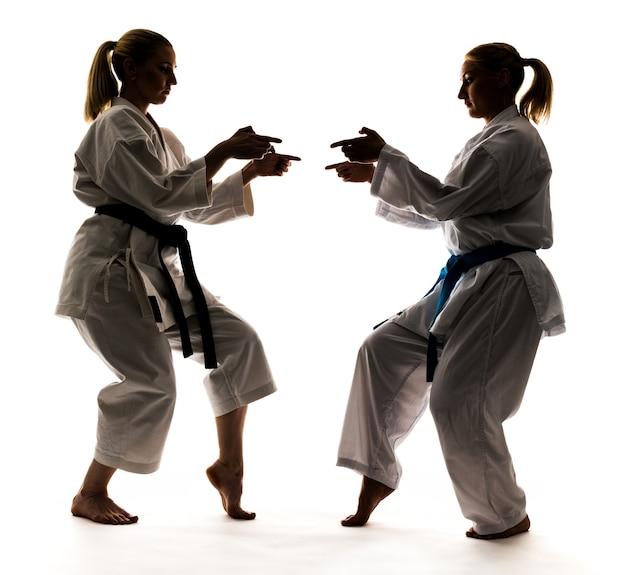 Starke junge blonde mädchen trainieren in einem kimono auf weißem hintergrund. junges paar profisportler.
