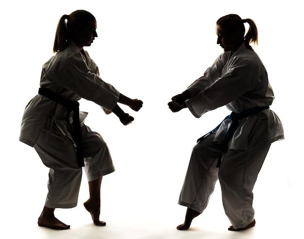 Starke junge blonde mädchen trainieren in einem kimono auf weißem hintergrund.