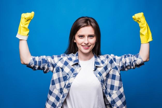 Starke junge frau, die arme hebt und bizeps zeigt, während sie gelbe gummihandschuhe für händeschutz während der reinigung isoliert trägt