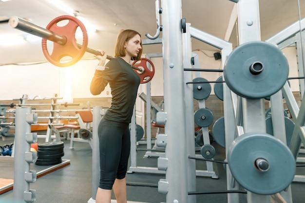 Starke junge frau, die schwergewichtstraining in der turnhalle tut