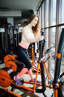Starke junge schöne frau ist in einem fitnessstudio auf einem ellipsoid beschäftigt.