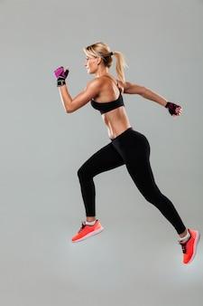 Starke junge sportfrau läuft isoliert