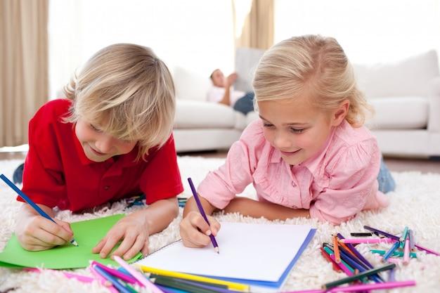 Starke kinder, die das lügen auf dem boden zeichnen