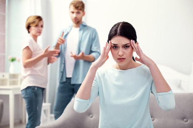 Starke kopfschmerzen. unglückliche depressive frau, die ihre schläfen berührt, während sie sich depressiv fühlt