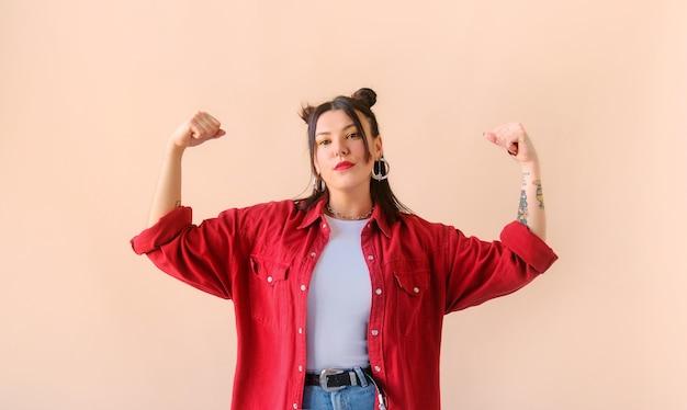 Starke, kraftvolle, stylische frau mit tattoo zeigt bizeps feminismus und frauenpower