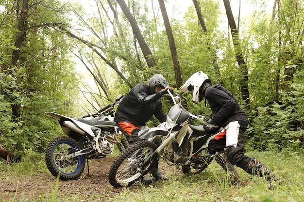 Starke männer in helmen heben gemeinsam im wald motorrad auf, während sie offroad-fähigkeiten üben