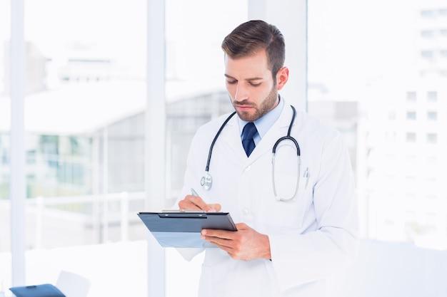 Starke männliche doktorschreibensberichte im klemmbrett