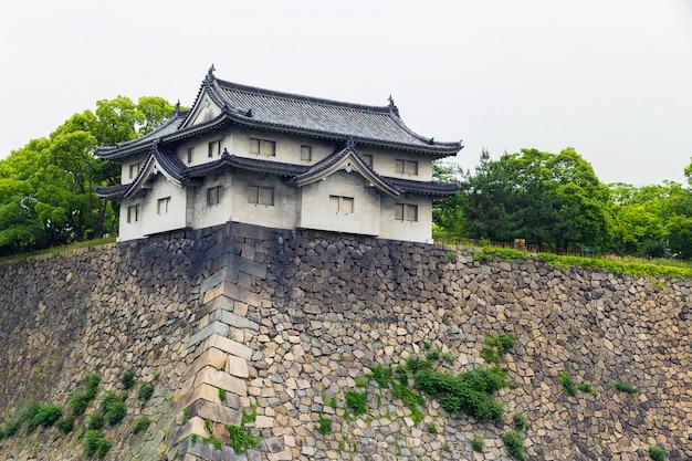 Starke mauern der burg von osaka und traditionelles japanisches gebäude