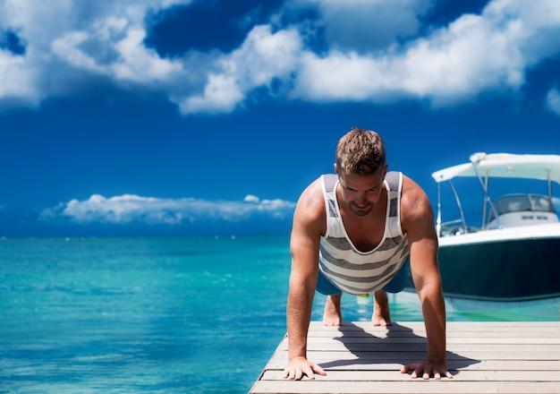 Starke muskulöse sportler auf einem ozeandock, die jeden tag trainieren. disziplin ist der schlüssel, auch an heißen sommertagen.