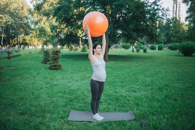 Starke oyung schwangere frau, die auf yogakameraden im park trainiert. sie hält einen großen orangefarbenen fitnessball in den händen über dem kopf.