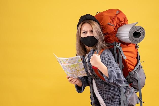Starke reisende frau mit schwarzer maske, die karte hält