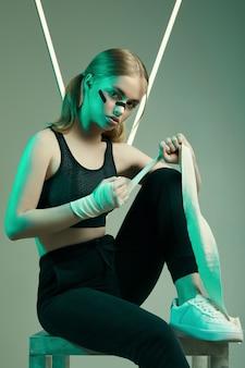 Starke schöne frau mit blonden haaren, selbstbewusstem blick, fäuste in schützenden boxverbänden