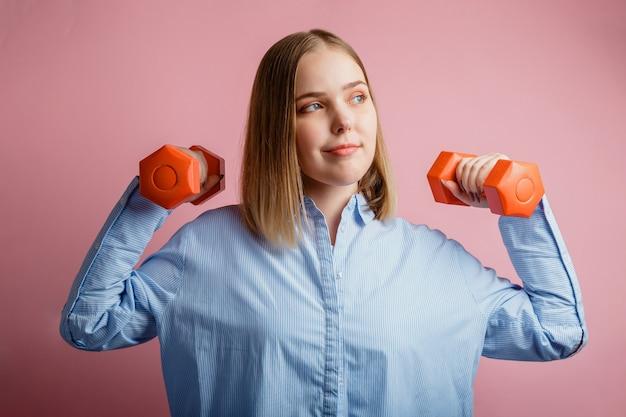 Starke selbstbewusste geschäftsfrau mit hanteln in bürokleidung isoliert auf rosa hintergrund