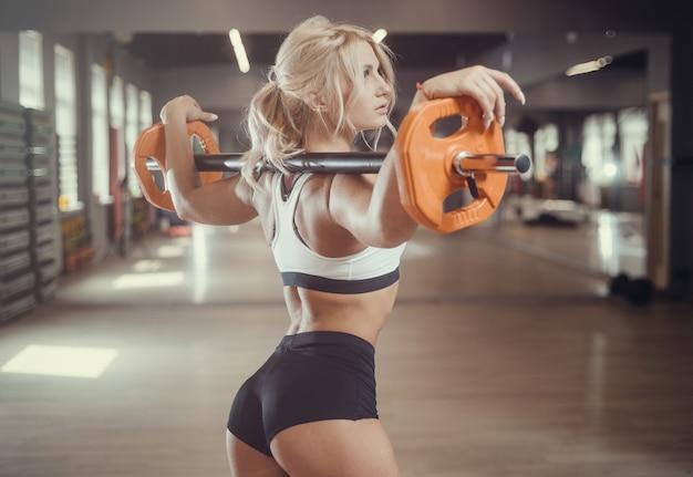 Starke sexy athletische junge frau, die im fitnessstudio trainiert