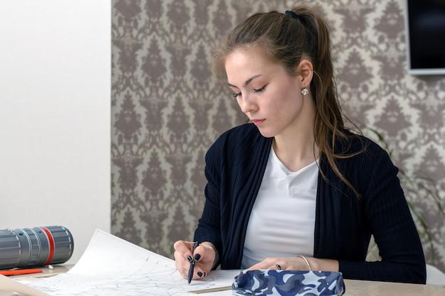 Starke studentinarchitekten-zeichnungsskizzen auf dem weißen segeltuch, das für den desktop sitzt.