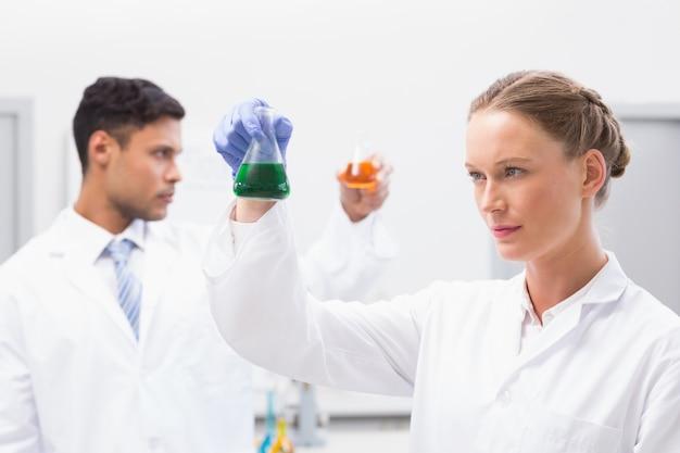 Starke wissenschaftler, die becher mit flüssigkeit halten