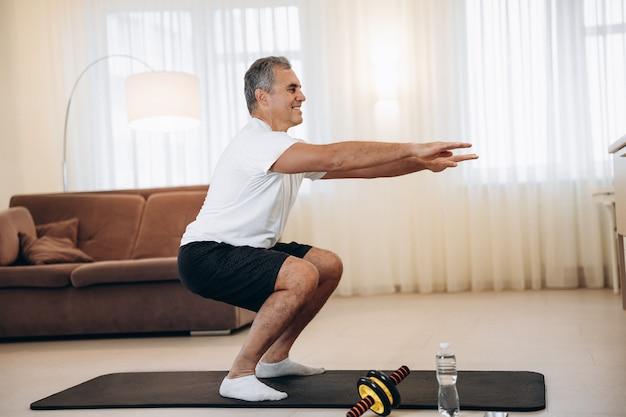 Starker älterer mann, der zu hause in seinem hellen wohnzimmer kniebeugenübungen macht