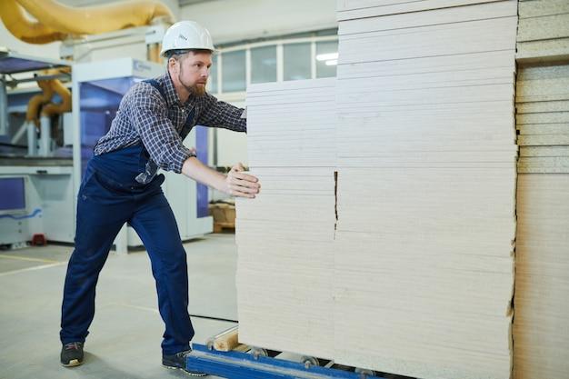 Starker arbeiter, der stapel von holzstücken auf rollenförderer drückt