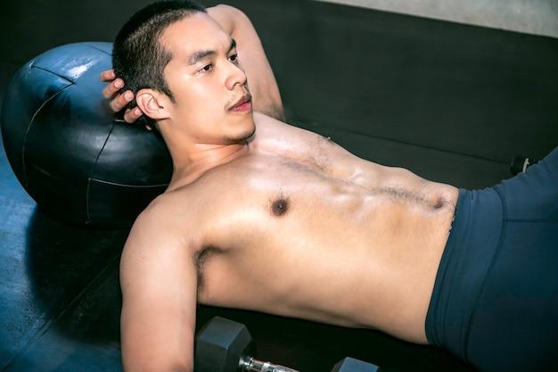Starker asiatischer mann in der sportkleidung, die an der eignungsturnhalle aufwirft.
