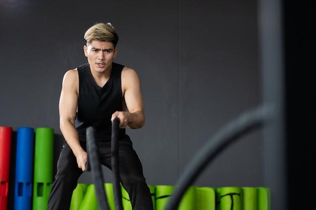 Starker asiatischer sportlicher mann, der in einer bereiten position für eine kampfseilübung in einem innengymnastikraum mit copyspace steht. leistungsstarker junger sportler, der ein bodybuilding-konzept, muskelaufbau trainiert.