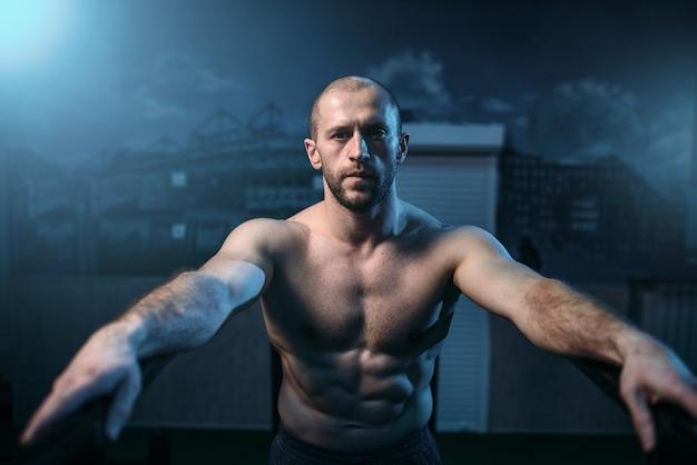 Starker athlet auf gymnastikstangen im fitnessstudio