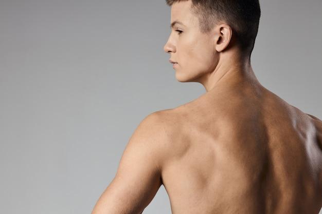 Starker athlet mit praller armmuskulatur nackter rückenansicht grauer hintergrund